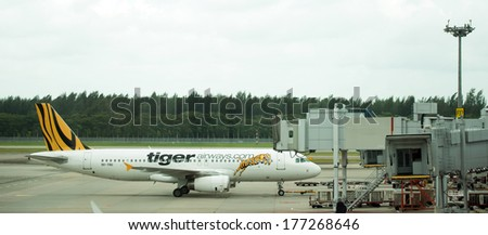 SINGAPORE - JAN 14: Tiger Airway aircraft docked at Changi Internation Airport terminal, Singapore on Oct 14, 2014. - stock photo