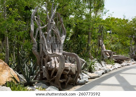 SINGAPORE - JANUARY 27, 2015: Decorative chair made of trunks, branches and roots of trees. Several similar chairs set in the park Gardens By The Bay  in Singapore.  - stock photo