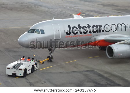 SINGAPORE - JANUARY 10:  Jetstar Asia Airbus 320 being pushed back for departure at Changi Airport on January 10, 2015 in Singapore - stock photo