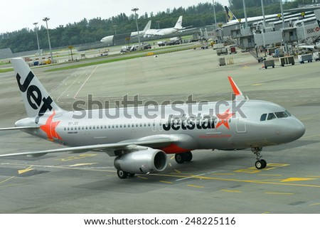 SINGAPORE - JANUARY 10: Jetstar Asia Airbus 320 low cost carrier taxiing to gate at Changi Airport on January 10, 2015 in Singapore - stock photo