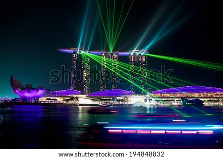 SINGAPORE - JANUARY 24: Marina Bay Sands hotel at night on January 24, 2014 in Singapore. Wonderful show is the largest light and water spectacle in Southeast Asia - stock photo