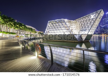 SINGAPORE - JANUARY 13: The futuristic building housing Louis Vuitton store reflect on the quiet waters of Singapore bay at twilight circa January 13, 2014 in Singapore. - stock photo