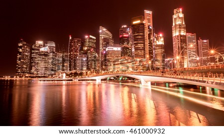 SINGAPORE - JULY 25, 2016_Business buildings shining beams of light at night time around Marina Bay in Singapore.
