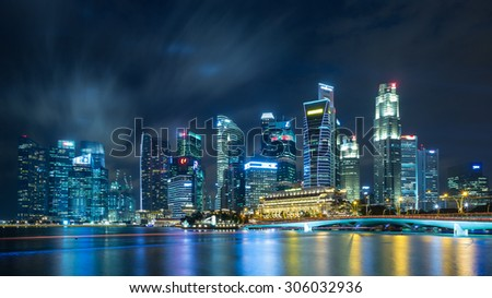 SINGAPORE - JULY 31_Business buildings shining beams of light at night time around Marina Bay on July 31, 2015 in Singapore.