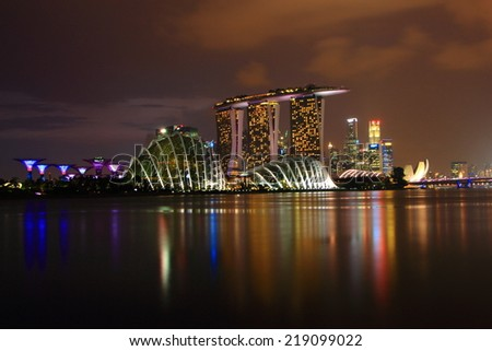 SINGAPORE - July 11: Night view of skyscrapers in Marina Bay on July 11, 2014 in Singapore. Singapore is the world's fourth leading financial center. - stock photo