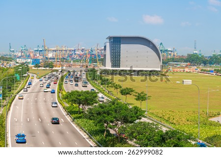 SINGAPORE - 01 JUN 2013: Cars traffic on Sheares ave with Singapore cargo port on background. Currently it is the world's second-busiest port in terms of total shipping tonnage. - stock photo