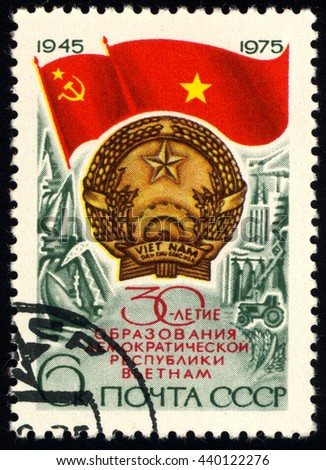 SINGAPORE â?? JUNE 21, 2016:  A stamp printed in the USSR shows Flag USSR and Flag and Arms to North Viet Nam, 30th anniversary , circa 1975 - stock photo