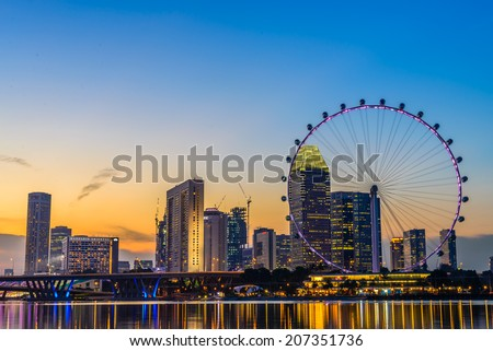 Singapore - June 23, 2014: View from distance to Singapore Flyer, huge ferries wheel and famous hotel and casino at Bayfront of Singapore. is round about 200 meters high and 340 meters wide. - stock photo