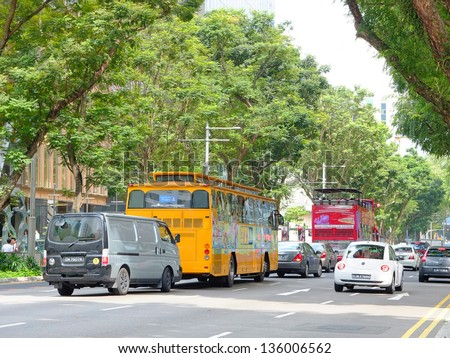 SINGAPORE - MARCH 8: Cars and buses on famous Orchard road on March 8, 2013 in Singapore. This 2.2 kilometer street is the retail and entertainment hub of Singapore and major tourist attraction. - stock photo