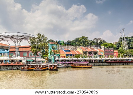 SINGAPORE - MARCH 18: Colorful bars and restaurants dot the Singapore River along Clarke Quay Mar. 18, 2015. The area used to be a commercial center during the colonial era. HDR rendering. - stock photo