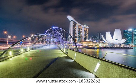 SINGAPORE - March  27: Helix Bridge and Marina Bay Sands on March 27, 2014. At night, the Helix Bridge is illuminated by a series of lights creating a special visual experience for the visitors. - stock photo