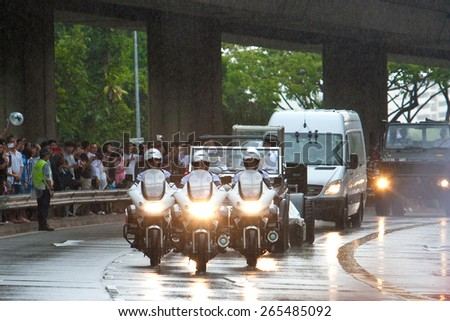 SINGAPORE MARCH 29:Motorcade leading gun carriage bearing the coffin of ex prime minister of Singapore, Mr Lee Kuan Yew driving pass on rainy day of state funeral Mar 29 Singapore 2015 - stock photo