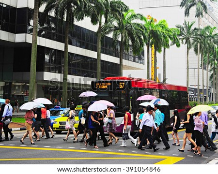 SINGAPORE - MARCH 06, 2013: People crossing the street in the rain in Singapore Downtown Core. There are more than 7,000 multinational corporations from US States, Japan and Europe in Singapore - stock photo