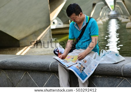 Singapore - March 14, 2013: The man is sitting at the sidewalk to read the newspaper