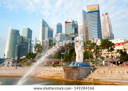 SINGAPORE - MARCH 08: The Merlion fountain spouts water in front of the Singapore skyline on March 08, 2013 in Singapore. Merlion is a creature with a lion head, often seen as a symbol of Singapore  - stock photo