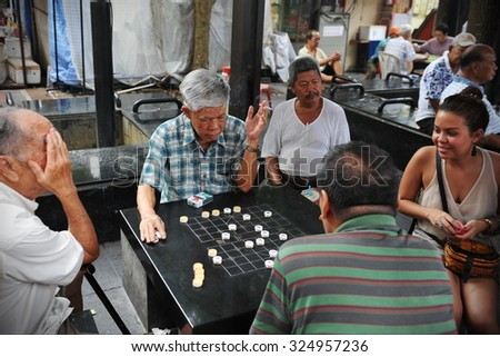 SINGAPORE - MAY 10: Men play checkers on a street in the city state's Chinatown district on May 10, 2013 in Singapore. Ethnic Chinese began settling in Chinatown circa 1820. - stock photo