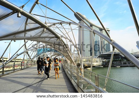 SINGAPORE - MAY 03: The Helix Bridge and Marina Bay Sands on May 03, 2013 in Singapore. The Helix is fabricated from 650 tonnes of Duplex Stainless Steel and 1000 tonnes of carbon steel. - stock photo