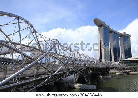 SINGAPORE - MAY 10: The Helix Bridge and Marina Bay Sands on May 10, 2014 in Singapore. The Helix is fabricated from 650 tonnes of Duplex Stainless Steel and 1000 tonnes of carbon steel. - stock photo