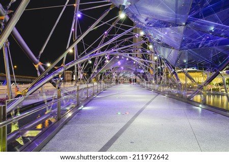 SINGAPORE - MAY 12: The Helix Bridge on May 12, 2014 in Singapore. Is a bridge in the Marina Bay. The Helix is fabricated from 650 tonnes of Duplex Stainless Steel and 1000 tonnes of carbon steel - stock photo