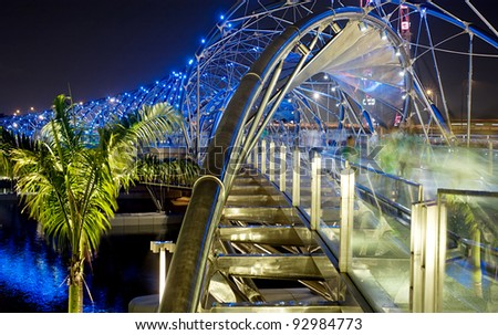 SINGAPORE - MAY 04: The Helix Bridge on May 04, 2011 in Singapore. Is a bridge in the Marina Bay. The Helix is fabricated from 650 tonnes of Duplex Stainless Steel and 1000 tonnes of carbon steel. - stock photo