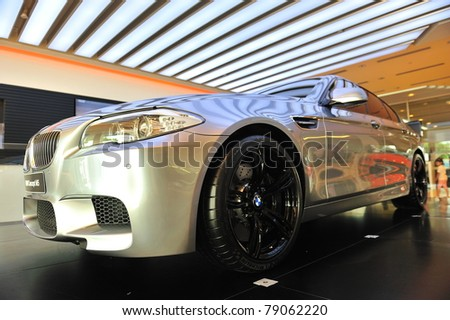 SINGAPORE - MAY 21: Unveiling the new BMW M5 Concept at Munich Automobiles BMW Service Centre Open House on May 21, 2011 in Singapore - stock photo