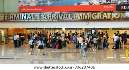 SINGAPORE - NOV 12: Travelers enter immigration control at Changi International Airport on Nov 12, 2011 in Singapore. Changi is a main aviation hub in SE Asia, handling 66 million passengers per year. - stock photo