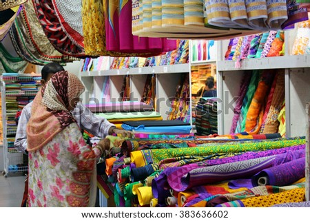 SINGAPORE/SINGAPORE - CIRCA NOVEMBER 2015: Lady with hijab buying colorful materials in Singapore's Little India district during Deepavali festivities - stock photo