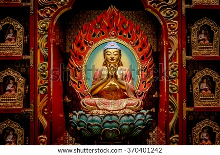 SINGAPORE/SINGAPORE - 23 DEC, 2015: Statue of Buddha sitting in meditation and waiting for Nirvana with hands in ritual gesture. Inside the Buddha Tooth Relic Temple. - stock photo