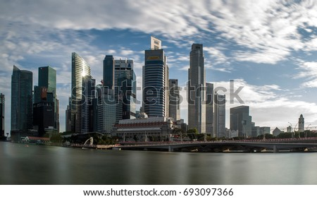 Singapore, Singapore - July 03, 2017: Pedestrians walk along bridge near Marina bay in Singapore with Singapore skyscraper and Merlion park in background