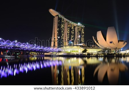 Singapore, Singapore - June 03, 2016: Night view of the pedestrian Helix Bridge, a structure of glass and stainless steel leading to the Marina Bay Sands Hotel.  - stock photo