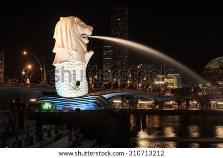 Singapore, Singapore - May 18, 2015: The Merlion statue in Singapore at night. The Merlion is a traditional creature in Singapore with a lions head and a body of fish. - stock photo