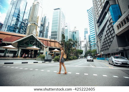 Singapore travel tourist woman on vacation  walking among the skyscrapers. Person in dress  over singapore city background . Asian summer destination