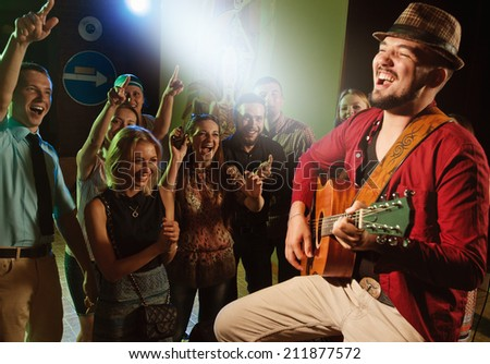 singer and guitarist performing on stage in a club in front of a cheering crowd - stock photo