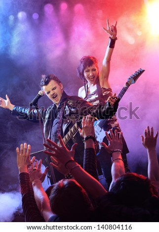 Singer and guitarist rocking out with the crowd enjoying it. - stock photo