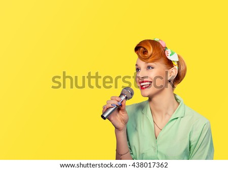 Singer. Closeup portrait head shot sexy beautiful happy young woman lady girl singing with microphone smiling isolated yellow background wall Positive human emotion expression feeling life perception  - stock photo