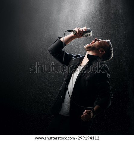 Singer performing with smoke and powder display in the background - stock photo