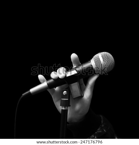singer right hand holding dynamic microphone, bw filter & isolated on black ( hand sign mean love ) concept = love to sing - stock photo