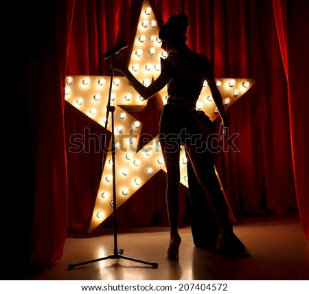 Singer woman on stage with broadway star on background - stock photo