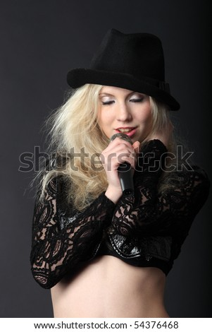 Singing blond girl in black hat with microphone