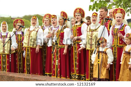 singing group of people in national Russian clothes in the park
