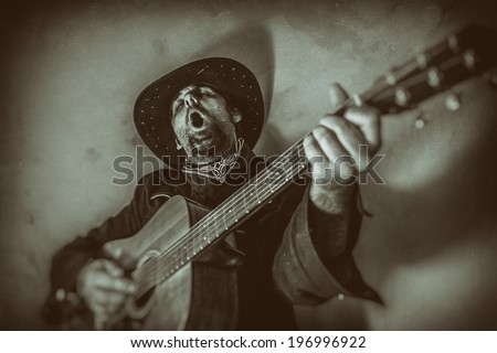 Singing Old West Cowboy With Guitar. Old west cowboy singing and playing a guitar, edited in vintage film style. - stock photo
