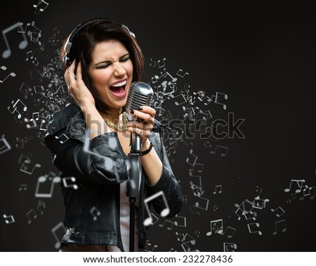 Singing song rock musician with microphone and earphones. Concept of rock music and rave - stock photo