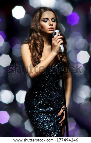 Singing woman in elegant dress with retro microphone. Beautiful glamour singer girl portrait with closed eyes against bokeh - stock photo