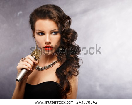 Singing Woman with Microphone. Beauty Glamour Singer Girl. Vintage Style. Song.Portrait of a glamorous girl holding a mike and singing - stock photo