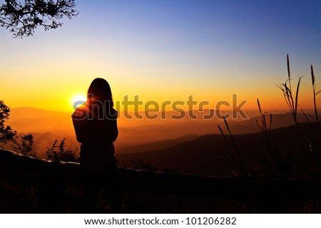 Single adult woman silhouette and sunset - stock photo