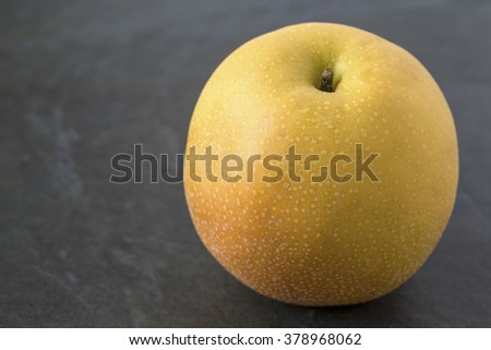 Single Asian Pear on the slate background - stock photo