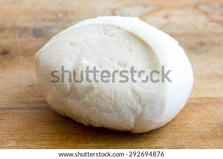 Single ball of mozzarella cheese on rustic wood surface. - stock photo