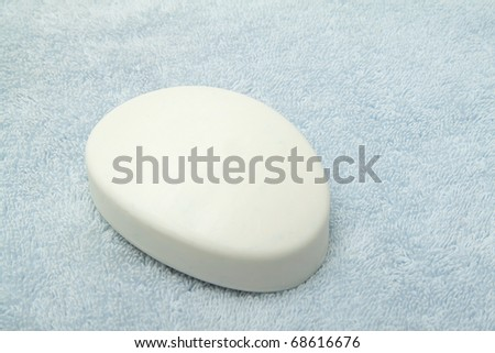 Single bar of white soap on the light blue towel