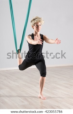 Single barefoot woman in black outfit with leg in green tarp suspended from ceiling doing aerial yoga workout for balancing - stock photo