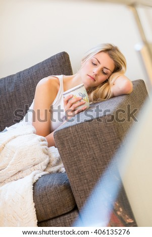 Single beautiful young woman in sleeveless shirt and white blanked laying on corner of sofa while holding coffee mug - stock photo